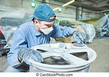 repair mechanic worker with light alloy car wheel disk rim