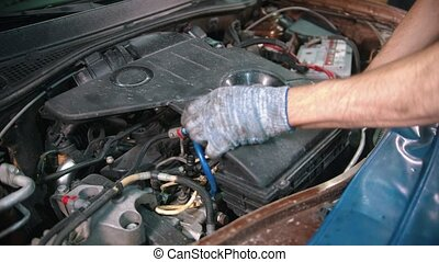 Auto repair shop - young man worker holding a cap of a big detail under the car hood
