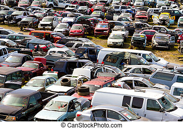 The scene shows many cars and other automobiles in a salvage junk yard where customers can pick and choose part for their vehicle repairs.