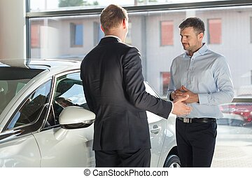 Auto seller discussing with client