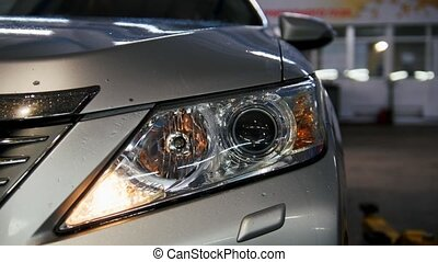 Auto service - checking headlights of car, close up