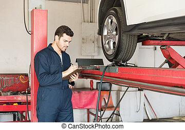 Auto Technician Making Checklist In Garage