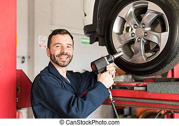 Auto Technician Using Impact Gun On Car Tire
