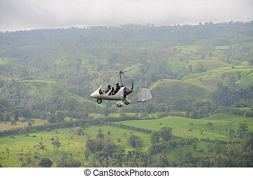 Autogyro flying above the tropical landscape