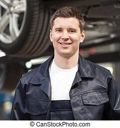 automático, mechanic., jovem, alegre, mecânico, sorrindo, câmera, enquanto, ficar, em, a, loja reparo