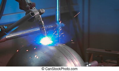 Automated electric welding on factory. Sparks fly in...