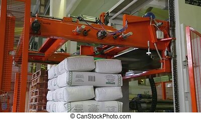 Automated process of stacking flour bags in stacks. Conveyor...