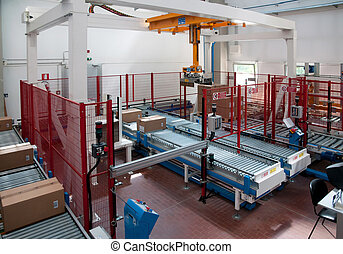 Automated warehouse with robots to prepare the pallets in a factory that produces components for electrical connections
