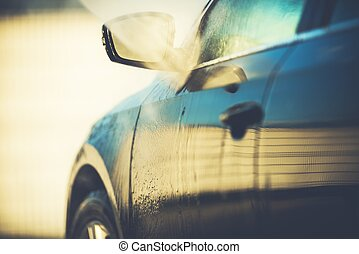 Automatic Car Wash Cleaning Closeup Photo Concept. Vehicle Under Heavy Water Spraying.