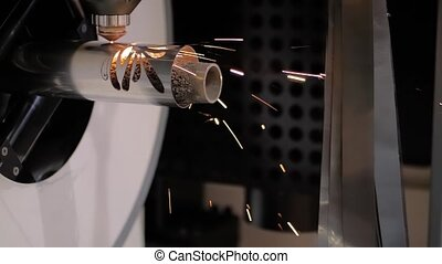 Automatic cnc laser cutting machine working with metal workpiece with sparks