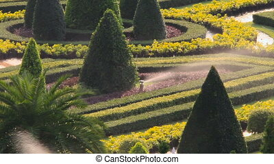 Automatic lawn watering device. Ornamental garden with landscape design. Nong Nooch Tropical Garden in Pattaya, Thailand.