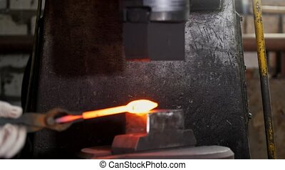 Automatic mechanical hammering - blacksmith forging red hot...