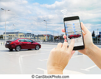 Automatic parking concept - hand holding and touching phone, parking a car automaticaly
