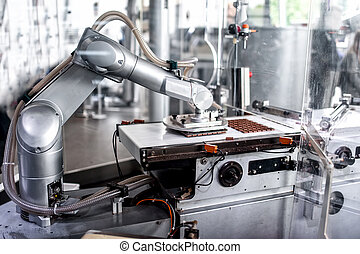 automatic robotic hand moving and preparing tiny bits of chocolate at chocolate factory. industrial chocolate factory with automatic robotic hand
