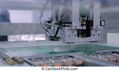 Automatic SMD pick and place machine during work - assembly of computer printed circuit board at factory. Automated technology, industrial, robotic, electronic, production, manufacturing concept