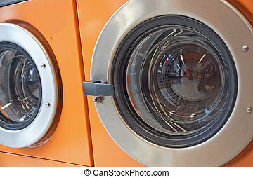 automatic washing machines in a laundromat - orange...