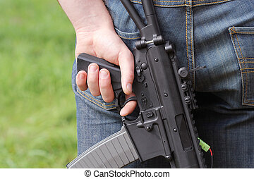 automatic weapon in hand of man