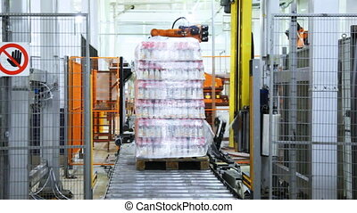 automatic wrapper cuts off end stretch film, and bottles of yogurt on pallet go roller conveyor