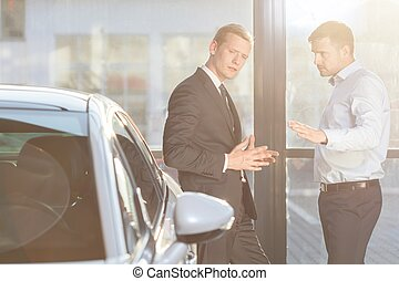 Automobile buyer discussing with seller
