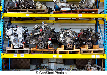 Car and truck engine block motors are lined up at an automobile salvage yard junkyard.