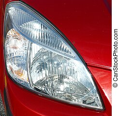 AUTOMOBILE HEADLIGHT - An automobile headlight against a red...