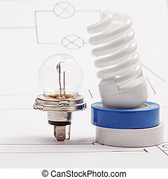 Automobile lamp and nergy saving lamp on a background of the electric scheme