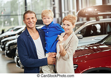 automobile sales centre. young family with child boy in car sell