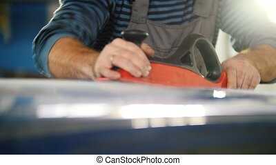 Automobile service - a worker polishes car, close up,...