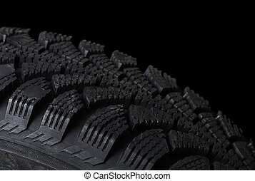 Automobile tire on black background