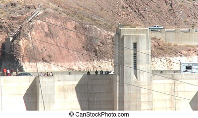 Automobiles and tourists cross the Hoover Dam
