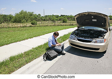 Horizontal view of a man working by the side of the road next to his broken down car.
