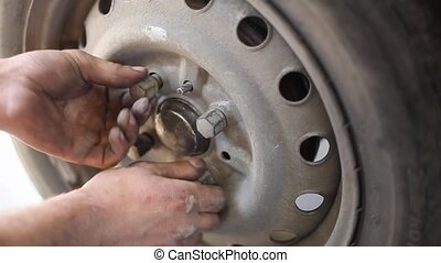 automotive - Car mechanic screwing wheel to car