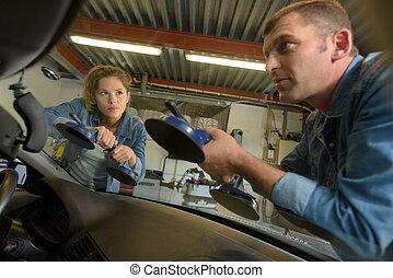 automotive glazier removing windscreen using suction