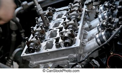 Automotive - Mechanic fixing cylinder head with camshaft of...