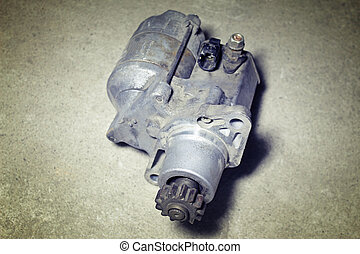 Automotive starter on a gray background