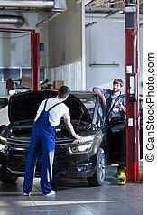 Automotive technician repairing a car in a garage