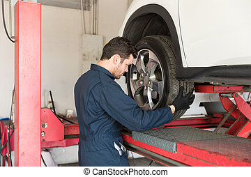Automotive Worker Changing Tire Of Car
