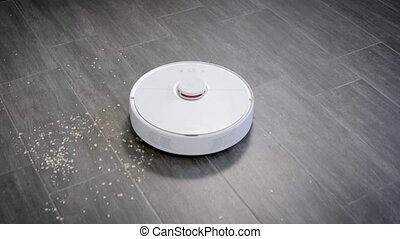 autonomous robotic vacuum cleaner is moving over floor in...