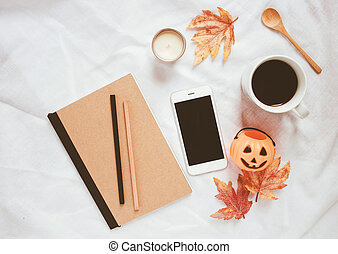 Autumn and halloween style concept, notebook and smartphone with coffee on white bed sheet background