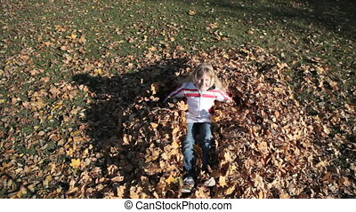 Autumn angel - Overview of a smiling girl falling on a heap...