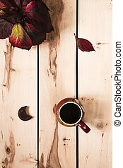 Autumn background. Cup of coffee on the table with leaves