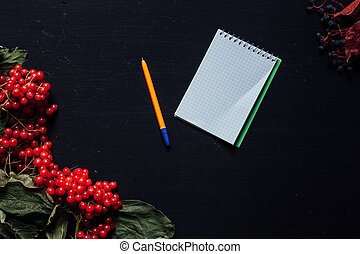 autumn background notebook yellow leaves red berries on a black background