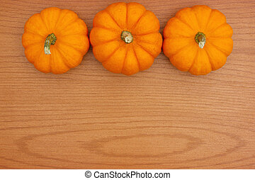 Autumn background with a pumpkins on wood