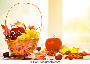 Autumn background with basket with yellow maple leaves, grapes, red apples. Frame of fall harvest on aged wood with copy space. Mock-up for seasonal offers and holiday post card