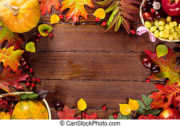 Autumn background with basket, yellow maple leaves, grapes, red apples. Frame of fall harvest on aged wood with copy space. Mock-up for seasonal offers and holiday post card
