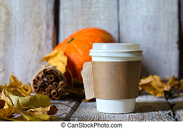 Autumn background with dry leaves and hot paper cup of coffee on wooden table.