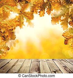 Autumn background with empty wooden board, fall yellow oak leaves and abstract bokeh light
