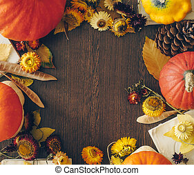 Autumn background with leaves and pumpkins. Frame of fall harvest on aged wood with copy space. Mockup for seasonal offers