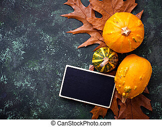 Autumn background with pumpkins and dried leaves