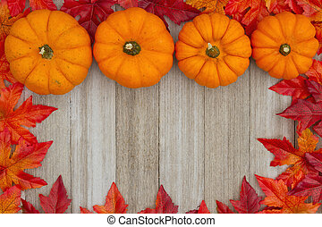 Autumn background with pumpkins and fall leaves on weathered wood